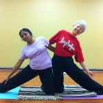 Radha and Sondra in a partnered Parighasana (Gate Pose)